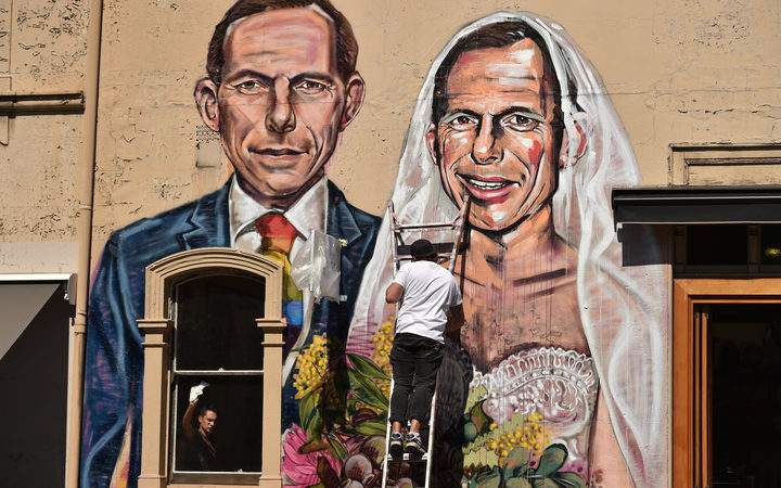 "Australian street artist Scottie Marsh paints a mural of former Australian prime minister Tony Abbott wedding himself in Sydney after Mr Abbott urged Australians to ""protect the family"" with their vote in the same-sex marriage postal survey."
