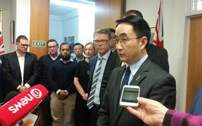 National Party MP Jian Yang speaking to reporters at a party office in Auckland.