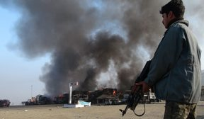 Afghan security personnel stand alert near burning NATO military vehicles after a clash between Taliban and Afghan security forces in 2013.