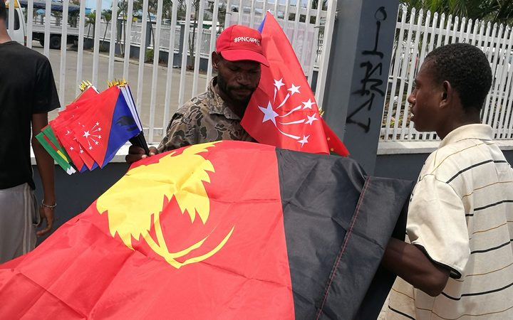 Man hawking national and provincial flags in Papua New Guinea.