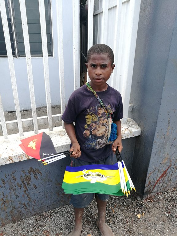Boy holding Papua New Guinea national and Morobe provincial flags.