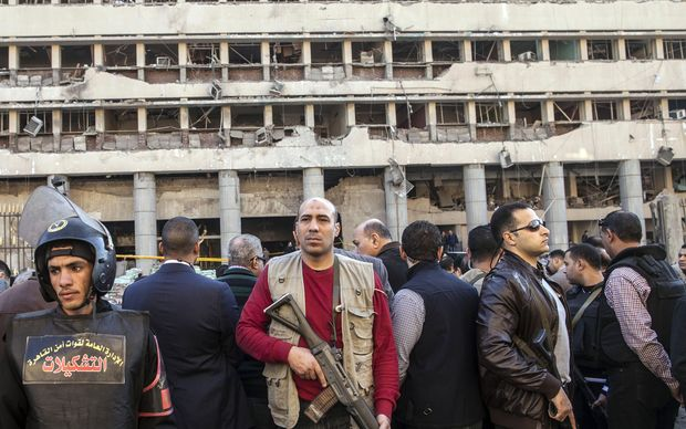 Police guard the damaged facade of the police headquarters in Cairo.