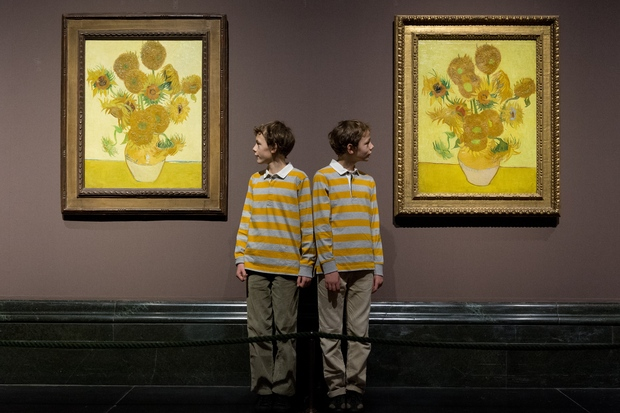 Identical twins Edgar and Gabriel with the sunflower paintings at London's National Gallery.