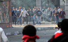Muslim Brotherhood supporters (background) clash rival pro-government demonstrators in Cairo on Saturday.