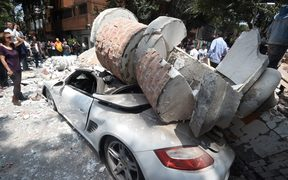 Rubble from a quake-hit building crushed a car in Mexico City.