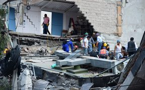 People search a collapsed building in Mexico City.