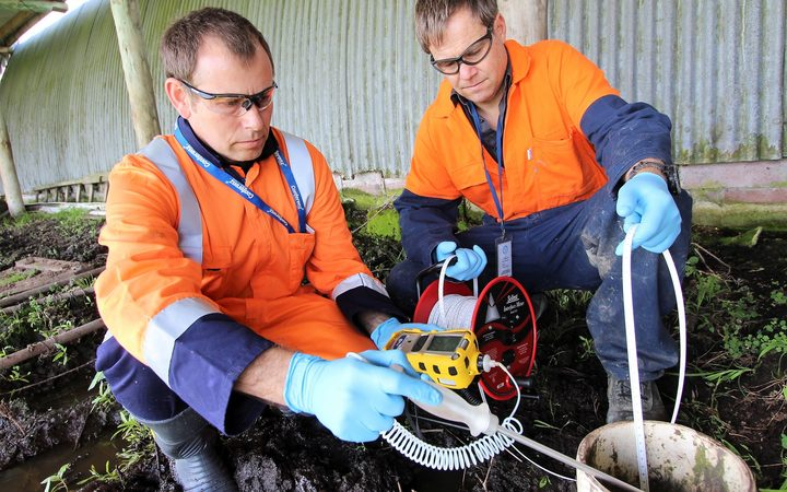 Northland Regional Council staff taking bore water for testing after the pipeline break at Ruakaka.
