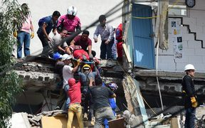 Rescuers pulling a woman alive from the rubble of a Mexico City building.