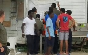Manus refugees checking the detention noticeboard