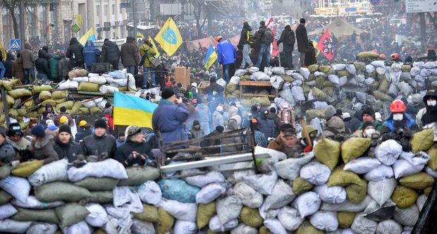 Anti-government protesters gather at a road block in central Kiev on Sunday.