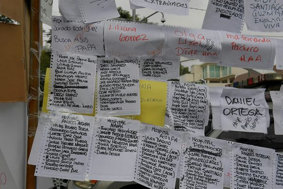 Lists of people and the hospitals they are in are posted near a school where at least 21 children died and 30 are missing.