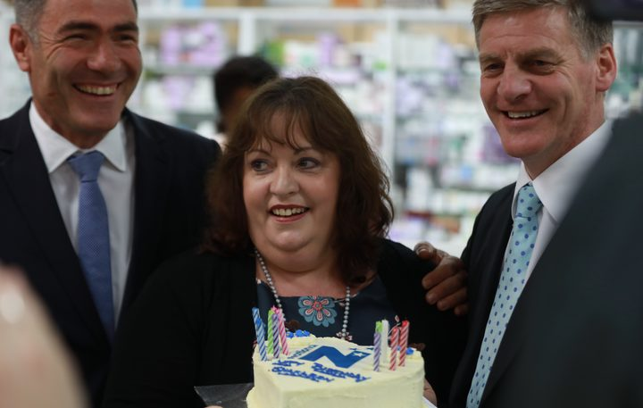 National Party leader Bill English, celebrates the birthday of a pharmacy employee, centre, during National's bus tour on Thursday. National MP Nathan Guy at left.