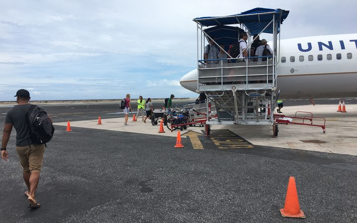 Steady out-migration to the United States is a major factor contributing to minimal population growth in the Marshall Islands. Here, passengers board a United Airlines flight departing Majuro.