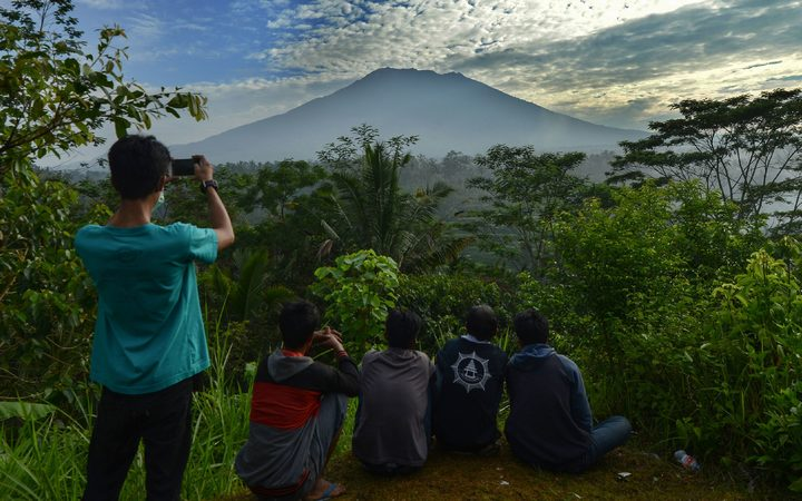 People look at Mount Agung in Karangasem on island of Bali, after warnings a volcanic eruption was imminent.