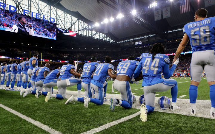 Members of the Detroit Lions take a knee during the playing of the national anthem before the start of a game at Ford Field in Detroit.