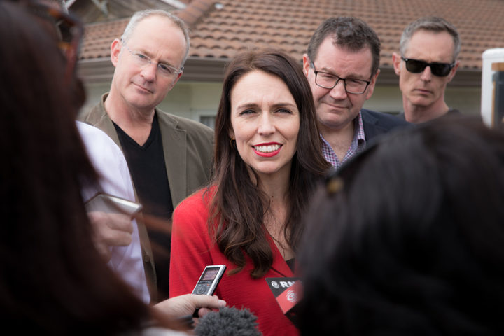 Jacinda Ardern (centre) speaking to media outside her home in Pt. Chevalier, Auckland. Phil Twyford (left) and Grant Robertson (right) stand with her.
