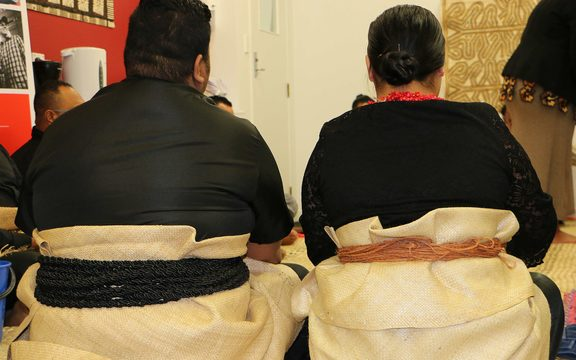 A back view of a seated Tongan man and woman in traditional dress, with mats wrapped around their waists.