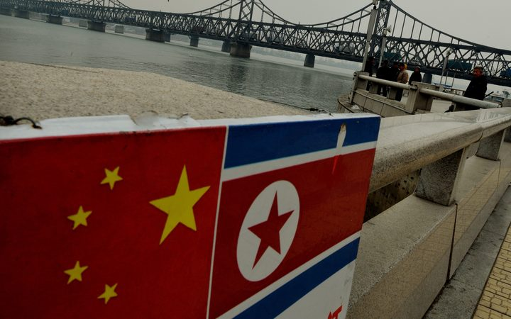 The Chinese and North Korean flags attached to a railing as trucks carrying Chinese-made goods cross into North Korea on the Sino-Korean Friendship Bridge at the Chinese border town of Dandong on December 18, 2013.
