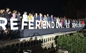 "People stand behind a sign translating ""Referendum Is Democracy"" during the closing meeting of the Catalan pro-independence groups and political parties that campaign for 'Yes' in the October 1 referendum on self-determination in Catalonia, at Montjuic fairground in Barcelona, Spain."