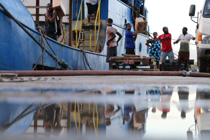Vanuatu disaster management staff loading donated goods onto a ship heading to Ambae to help with evacuations.