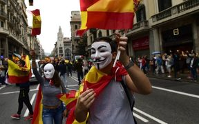 A man wearing a 'Guy Fawkes' mask holds a Spanish flag during a demonstration in Barcelona against independence in Catalonia.