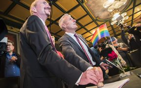 Bodo Mende (C) and Karl Kreile (L) stamp their wedding certificate during their wedding ceremony in Schoeneberg town hall in Berlin, Germany on October 1, 2017.