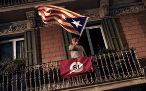 A man waves an 'Estelada' (Pro-independence Catalan flag) from a balcony after the closing of the 'Espai Jove La Fontana' (La Fontana youth center) polling station, on October 1, 2017 in Barcelona.