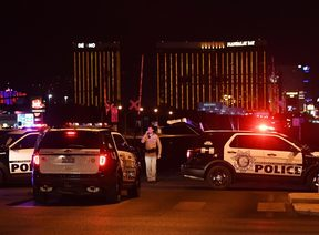 Police form a perimeter around the road leading to the Mandalay Bay hotel.