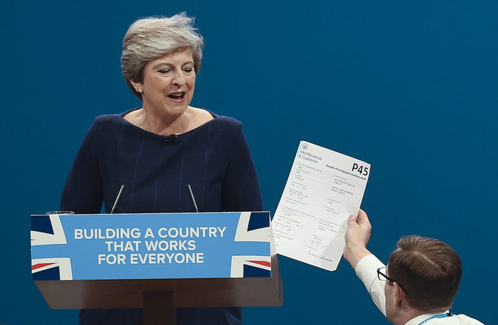 Comedian Simon Brodkin gives a mock P45 (employee leaving form) to Britain's Prime Minister Theresa May during her speech on the final day of the Conservative Party annual conference.