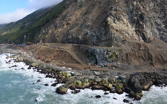 Aerial shot of huge cliff with workers cut back debris