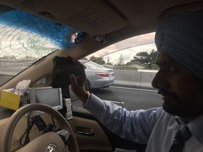 Balkar Singh holds the rock that was thrown from a motorway overbridge into his car.