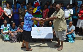 Collin Michael from the Ambae Disaster Relief Committee in Port Vila receives a donation from the Mini Games Organising Committee.
