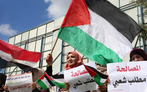Palestinians wave flags during a support rally for Palestinian reconciliation