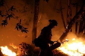 CalFire firefighter Brandon Tolp uses a drip torch during a firing operation near Calistoga, California.