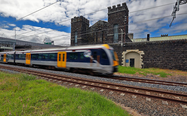 An Auckland Transport train passes by Mt Eden prison