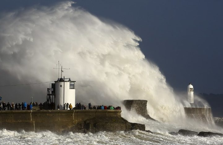 Huge waves strike the harbour wall and lighthouse at Porthcawl, South Wales, as storm Ophelia hits.