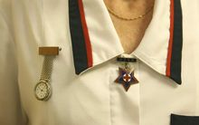 A registered nurse with uniform and badges.