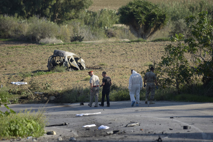 Police and forensic experts inspect the wreckage of Daphne Caruana Galizia's car.