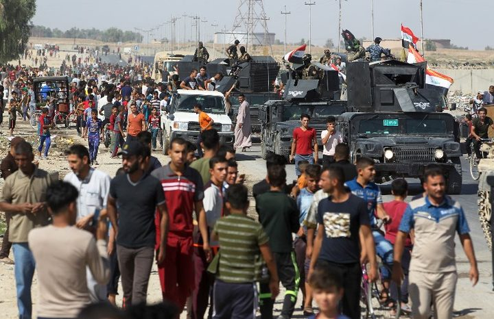Civilians gather as Iraqi forces arrive in the southern outskirts of Kirkuk.