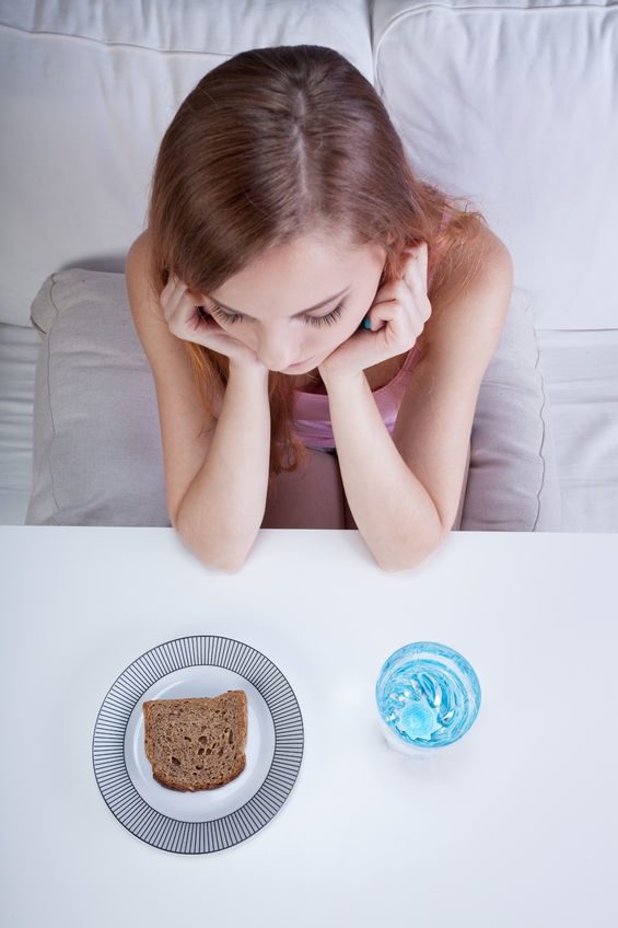 A photo of a girl looking at her dinner which is just bread and water