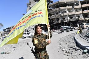 Rojda Felat, a Syrian Democratic Forces (SDF) commander, waves her group's flag at the iconic Al-Naim square in Raqa.