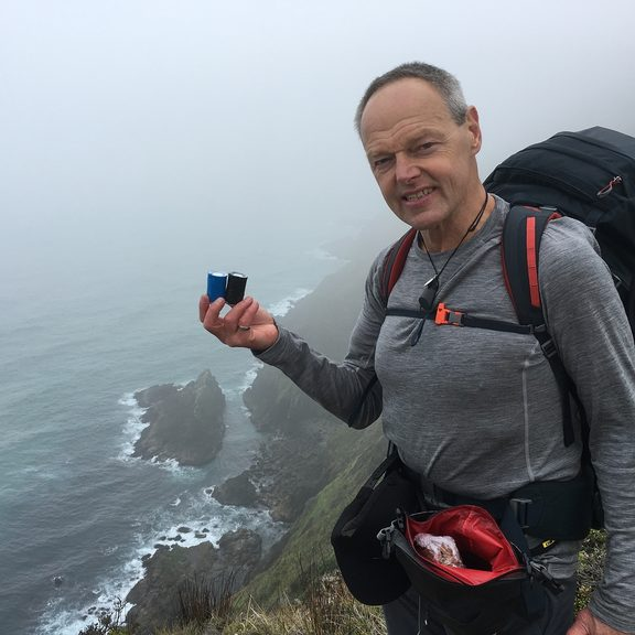 Bruce Hopkins at Cape Reinga holding the ashes of his father and brother.