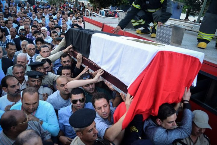 People carry the coffin of Egyptian police officer Mohamed Wahid, killed a day earlier in a shoot-out with suspected militants southwest of Cairo.