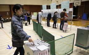 A woman casts her ballot for Japan's general election at a polling station in Tokyo.