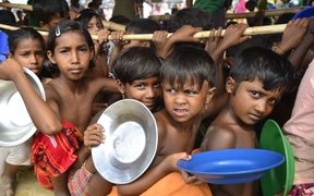 Rohingya refugee children wait to collect food at the Palongkhali makeshift Camp in Cox's Bazar, Bangladesh.