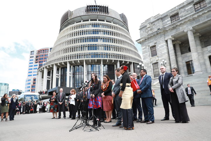 New PM Jacinda Ardern, flanked by her government, speaks to the public at Parliament.