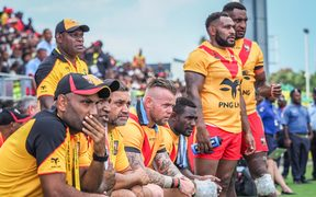 PNG Kumuls coach Michael Marum (L), assistant coach Marcus Bai (2L) and other watch on from the sideline.