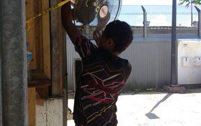A Manus Islander taking a fan from the detention centre.