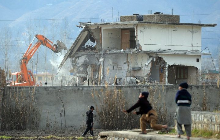 Young Pakistani boys play near demolition works on the compound where Al-Qaeda chief Osama bin Laden was slain.