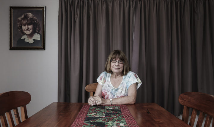 Robyn Jensen at home, 2017, under a photo of her missing daughter Kirsa.